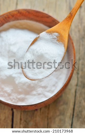 Close-up of Spoon of baking soda over bowl of baking soda - stock photo