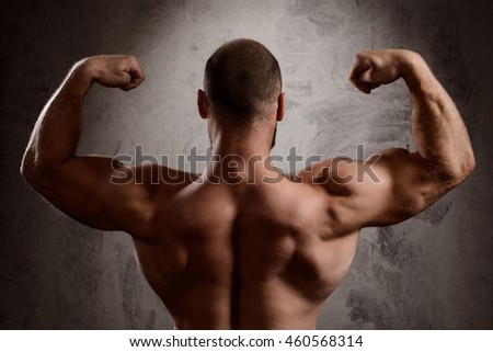 Close up of sportive man's body over dark background.