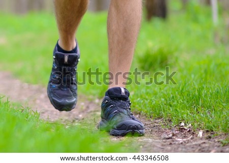 Close-up of Sportsman's Legs Walking on the Trail in the Wood. Active Lifestyle Concept