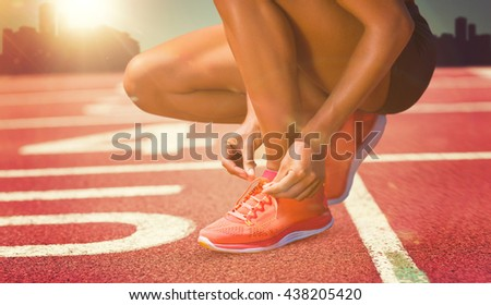 Close up of sportswoman is lacing shoes against composite image of race track