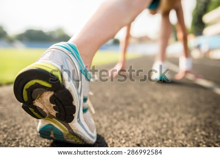 Close-up of sporty girl ready to run sprint. Female athlete in powerful starting line pose. - stock photo