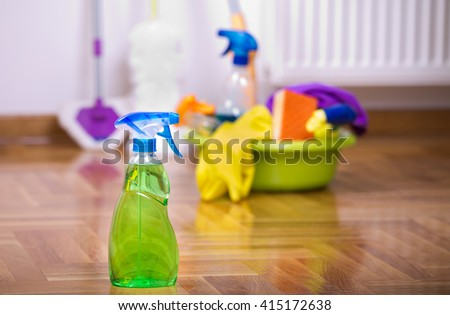 Close up of spray bottle for floor cleaning with different cleaning supplies and equipment in background - stock photo
