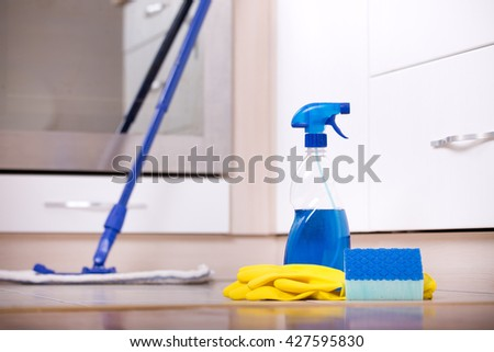 Close up of spray bottle, protective gloves and sponge on kitchen floor and oven in background. House cleaning concept - stock photo