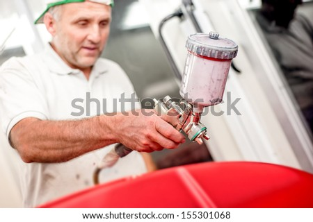 Close-up of spray gun and airbrush painting a red car