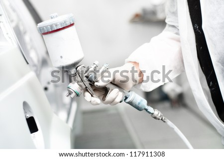 close-up of spray gun painting a car - stock photo
