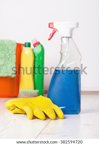 Close up of spraying bottle and rubber gloves on the bright wooden floor and cleaning supplies and equipment in background - stock photo