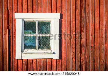 Close up of square white window in old red wooden barn wall, Sweden  - stock photo