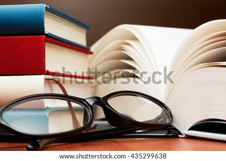 Close up of stack of books, large book pages and glasses. Glasses and books on wooden table.