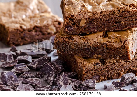 Close up of stack of homemade double chocolate chunk brownies sitting on wooden table with dark chocolate - stock photo