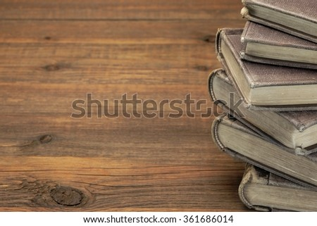 Close Up Of Stack Of Old Books With Copy Space On Wood Background - stock photo
