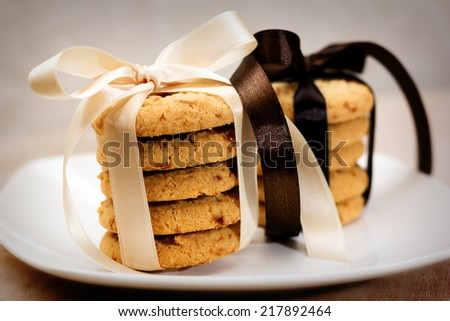Close up of stacked apple chip cookies taped with silk ribbons on white china plate - stock photo
