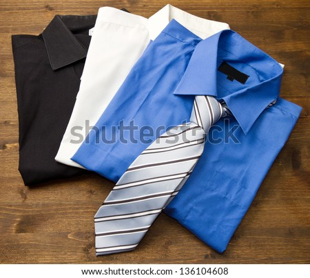 Close up of stacked shirts with tie on wood - stock photo