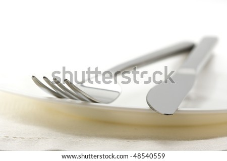 Close-up of stainless fork and knife on white plate with linen napkin. Selective focus on foreground. - stock photo