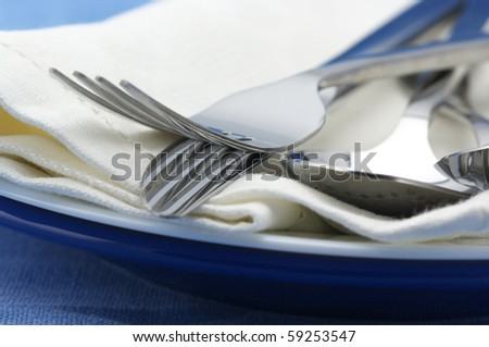 Close-up of stainless spoon, fork and knife on plate with linen napkin. Selective focus on foreground. - stock photo