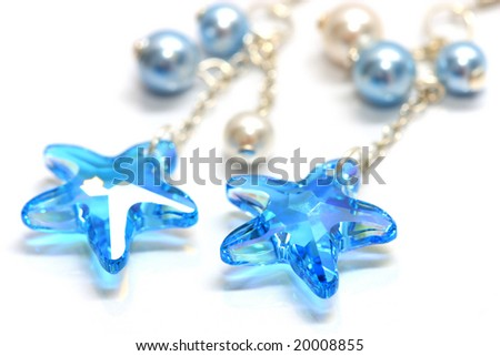 Close up of star shape bead earrings on white background.