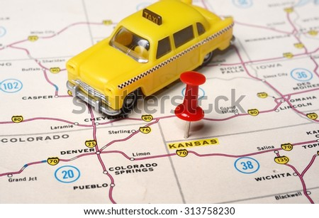 Close up of state Kansan USA map with red pin and a taxi toy - Travel concept - stock photo