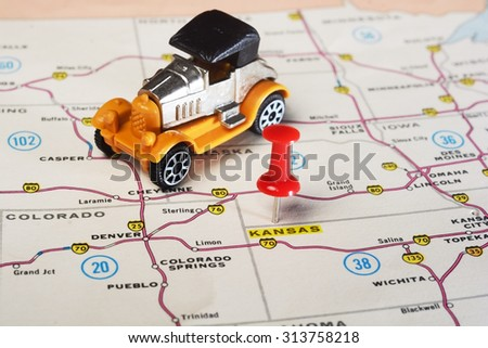 Close up of state Kansan USA map with red pin and retro toy car  - Travel concept - stock photo
