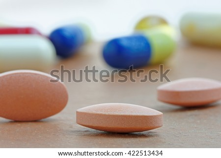 Close up of statin tablet or generic pill with out of focus tablets in background - stock photo