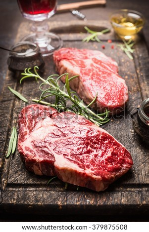 Close up of steak with rosemary and spices on dark rustic background. - stock photo