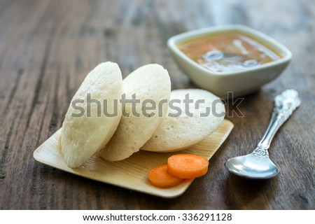 Close up of steamed idlis in an eco-friendly plate and bowl of spicy sambar. - stock photo