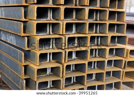 Close-up of steel channel U-sections bunch in warehouse - stock photo