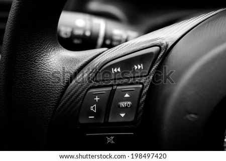 Close up of steering wheel of modern car. Volume and telephone command with cockpit background , black and white - stock photo