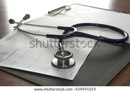 Close up of stethoscope and a waveform from an EKG test  - stock photo