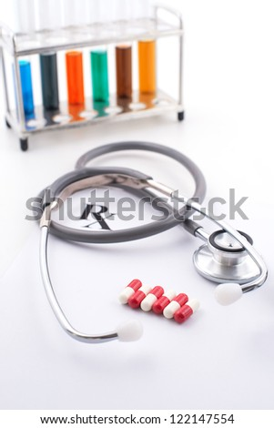 Close-up of stethoscope and capsules isolated on white - stock photo