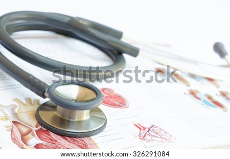 Close up of stethoscope on anatomy text book. - stock photo