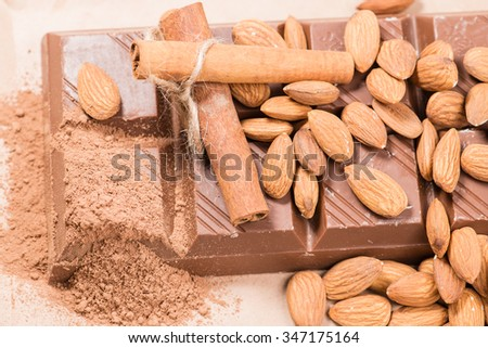 Close-up of still life: white and dark chocolate, almonds, cinnamon, cocoa. shallow DOF - stock photo