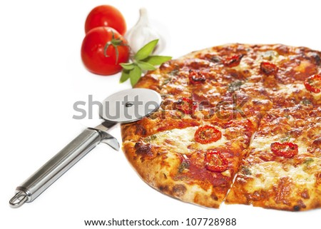 Close-up of stone backed pizza margarita with sun dried tomatoes and pesto with disk pizza knife.  isolated on white background