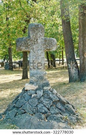 Close up of stone cross sign in a park area, on green grass background - stock photo