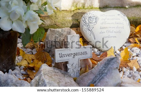Close up of stone heart and cross on tomb - stock photo