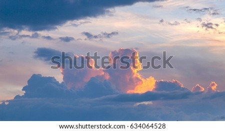 Close up of storm clouds, lit orange by the setting sun, Thailand