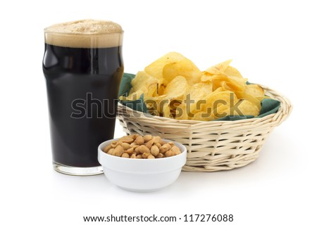 close up of stout with peanuts and chips - stock photo