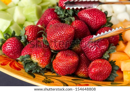 Close up of strawberries on serving platter of hors d'oeuvres of various fruits and cheeses - stock photo