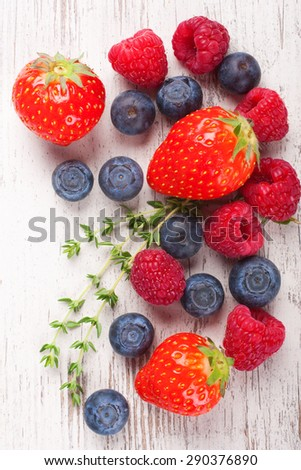 Close up of strawberry and other berries on White Wooden Background. Summer or Spring Organic Berry over Wood. Strawberries, Raspberries, Blueberry and thyme. Healthy food, Gardening, Harvest Concept. - stock photo