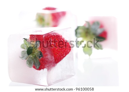 Close up of strawberry frozen in ice - stock photo
