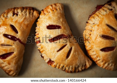 Close-up of Strawberry Hand Pies Fresh Out of the Oven on Parchment Paper - stock photo