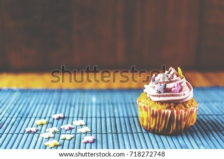close up of strawberry pink cupcake on blue mat on wooden background