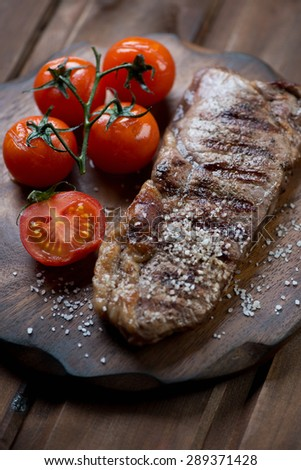 Close-up of striploin beef steak with grilled tomatoes and salt, selective focus - stock photo