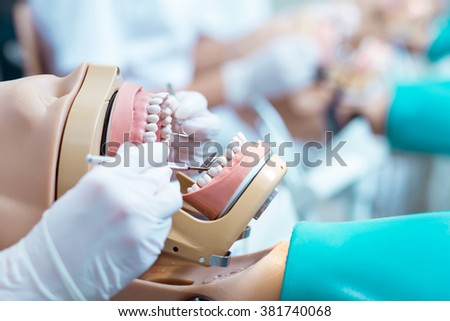 Close up of student in white gloves working on dental manikin