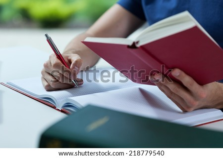 Close-up of student making his notes from the book - stock photo