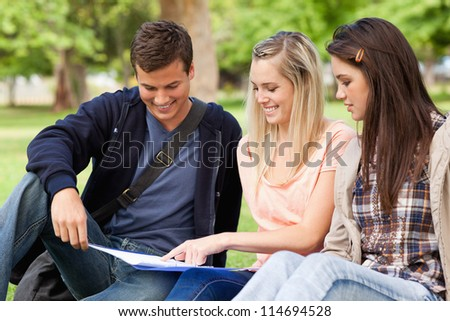 Close-up of students studying while sitting in a park - stock photo