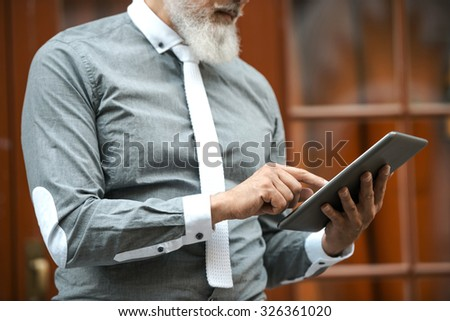 Close up of stylish handsome adult man with beard standing outdoors. Man using tablet computer - stock photo
