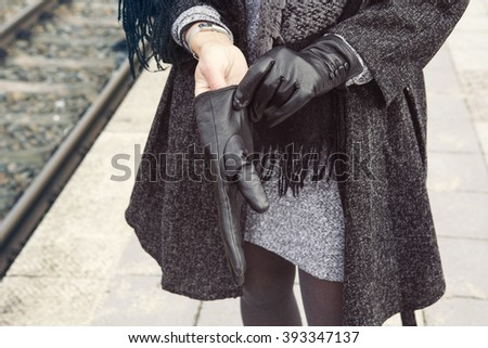 close-up of stylish woman at train station putting on her gloves