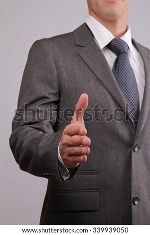 Close up of successful businessman with open hand gesturing a hand shake. Meeting new business partners, partnership, negotiations, presentation - stock photo