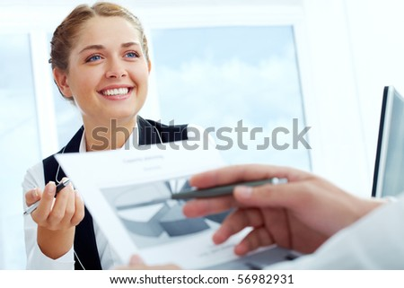 Close-up of successful businesswoman explaining something while discussing papers with colleague - stock photo