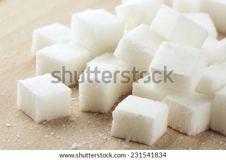 Close-up of sugar cubes on wood. - stock photo