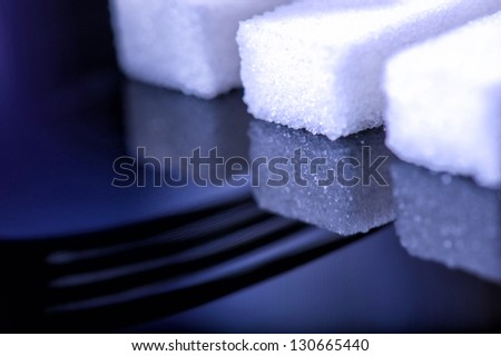 close up of sugar cubes with a fork shadow